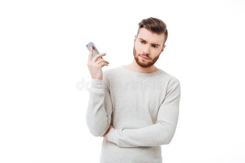 Jeune homme contrarié tenant le smartphone loin de son oreille Le ` fâché t de doesn d'homme veulent écouter parlant au téléphone photos libres de droits