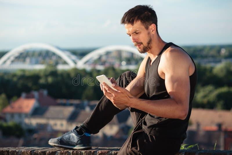 Jeune homme convenable déterminé à l'aide d'un téléphone intelligent, détendant après une séance d'entraînement photos libres de droits