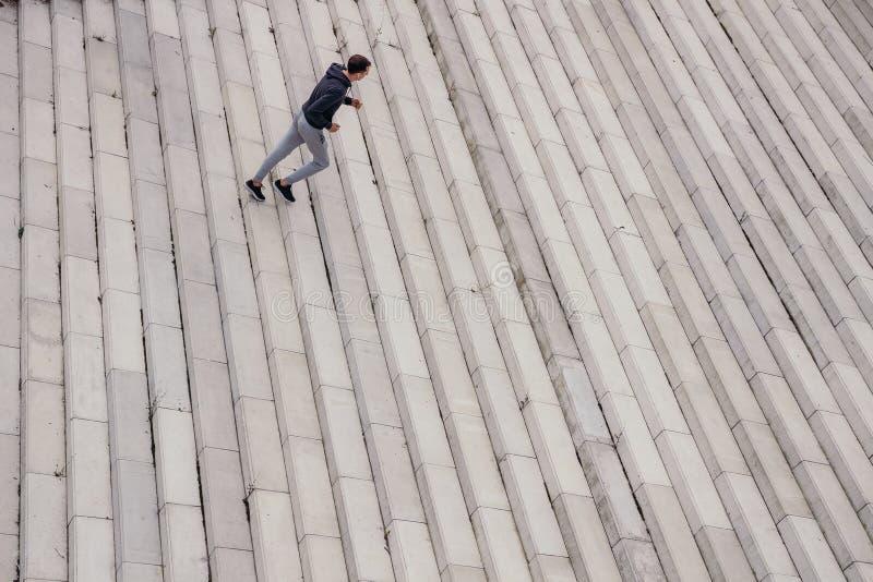 Jeune homme courant en haut dans la ville moderne image libre de droits
