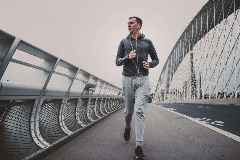 Jeune homme courant sur le pont moderne dans la ville, musique de écoute sur le smartphone photos stock