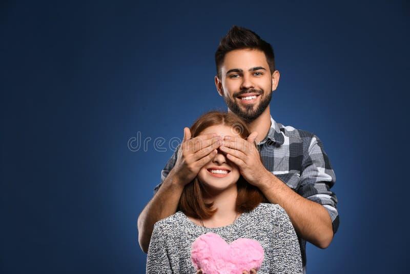 Jeune homme couvrant les yeux de son amie sur le fond de couleur Célébration de Saint-Valentin de saint photo libre de droits
