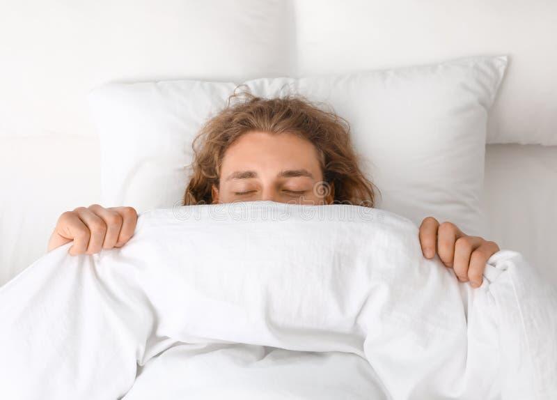 Jeune homme couvrant son visage de couverture tout en dormant sur l'oreiller bedtime photo stock