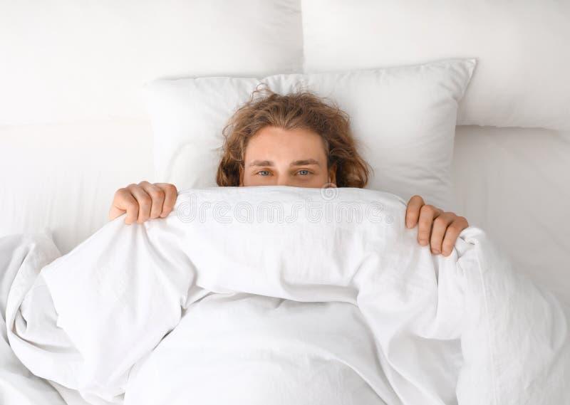 Jeune homme couvrant son visage de couverture tout en se trouvant sur l'oreiller, vue supérieure photos libres de droits