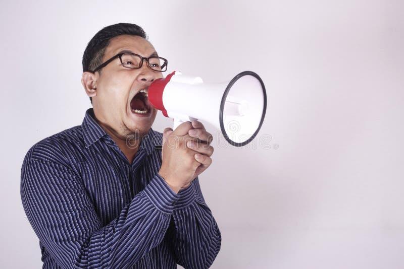 Jeune homme criant avec le m?gaphone, expression f?ch?e photographie stock libre de droits