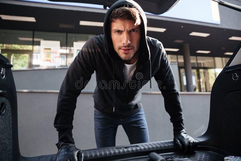Jeune homme criminel tenant et regardant le tronc de voiture photo stock