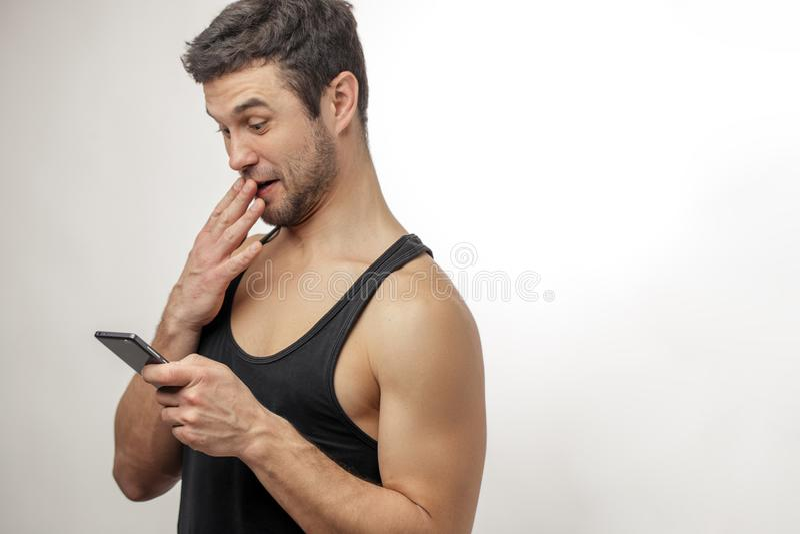Jeune homme curieux regardant son téléphone portable et fermeture sa bouche images libres de droits