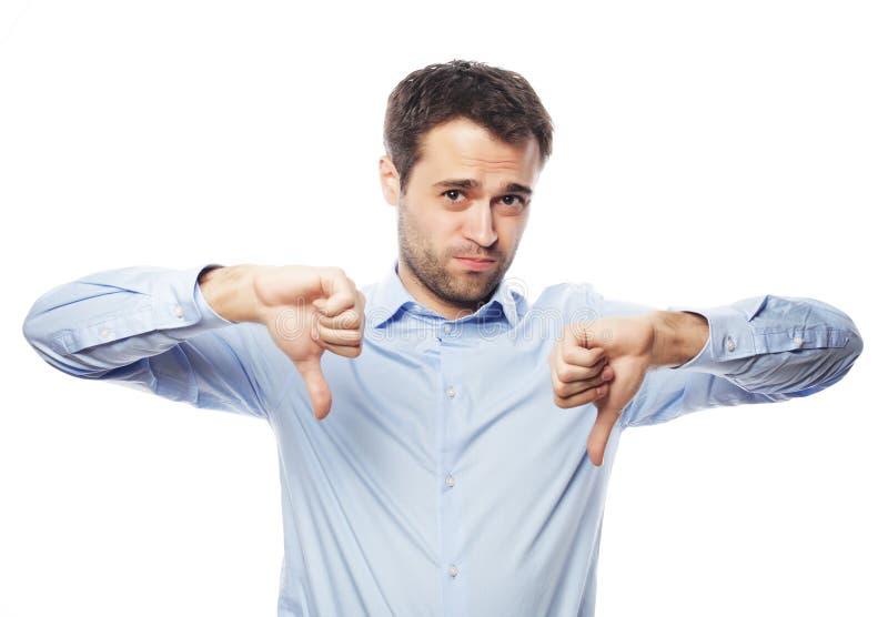 Jeune homme déçu d'affaires avec le pouce vers le bas photo stock