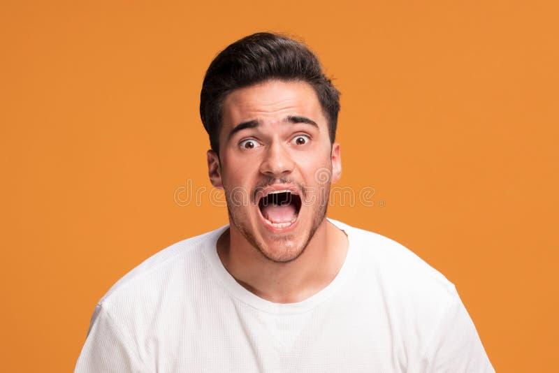 Jeune homme déçu sur le fond jaune images stock