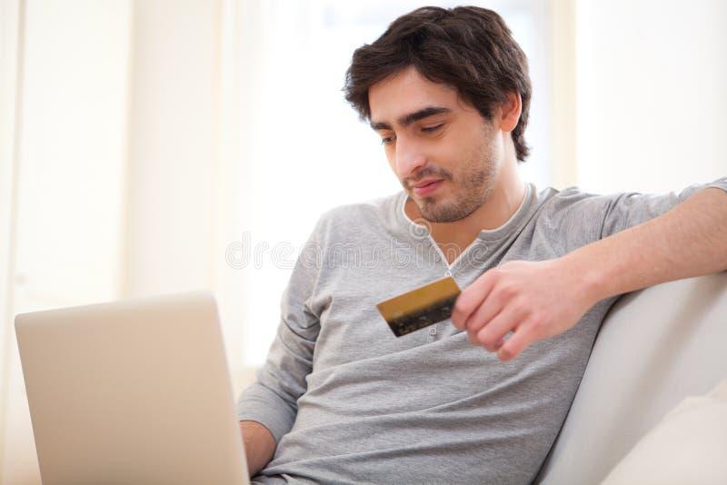Jeune homme décontracté payant en ligne avec la carte de crédit dans le sofa photo libre de droits
