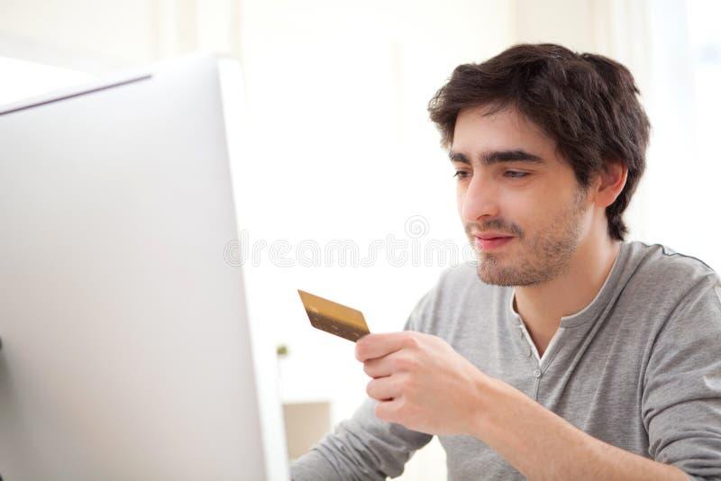 Jeune homme décontracté payant en ligne avec sa carte de crédit images stock