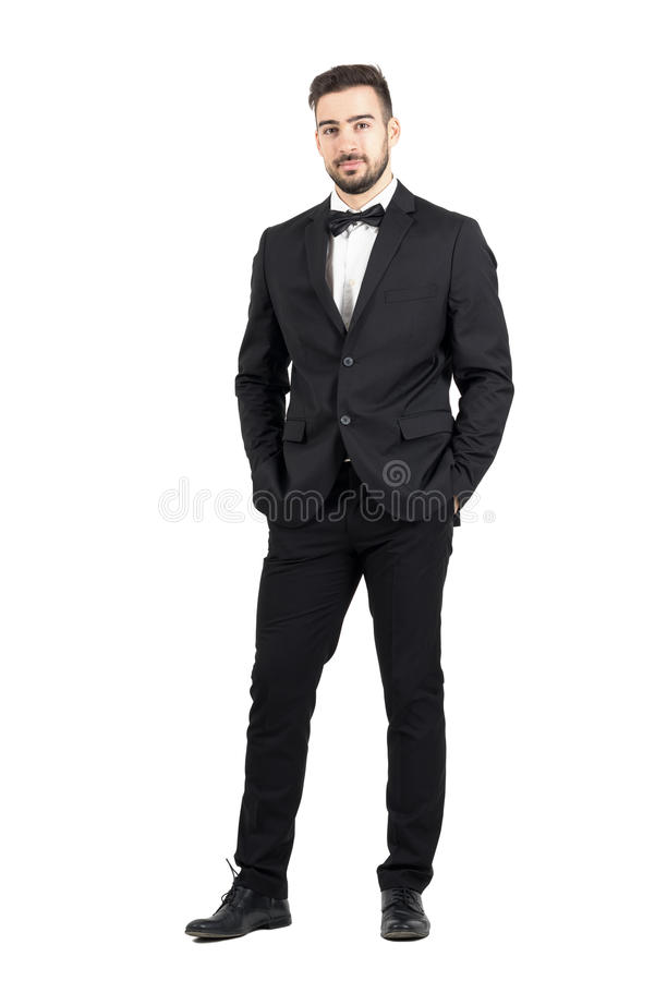 Jeune homme décontracté sûr riche dans le smoking regardant l'appareil-photo avec des mains dans des poches image stock