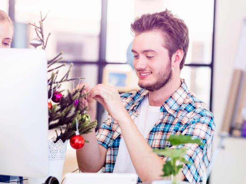 Jeune homme décorant l'arbre de Noël dans le bureau image stock