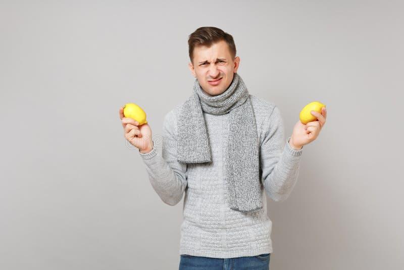 Jeune homme dégoûté dans le chandail gris, écharpe tenant des citrons sur le portrait gris de studio de fond de mur Sain images stock