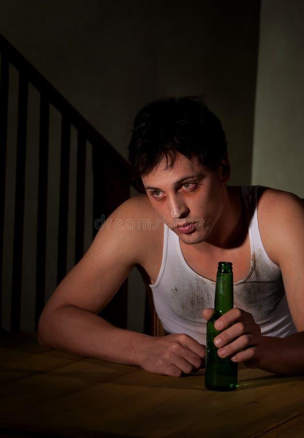 Jeune homme déprimé avec la bouteille à bière photographie stock libre de droits