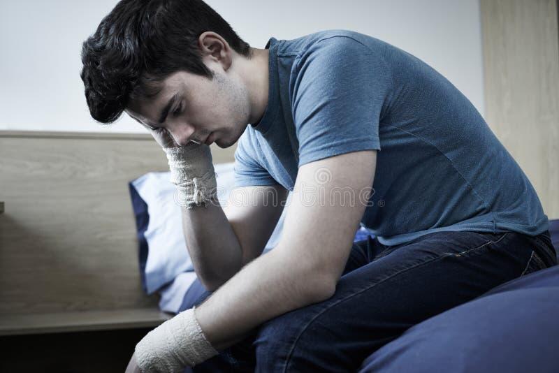 Jeune homme déprimé avec les poignets bandés après tentative de suicide photos libres de droits