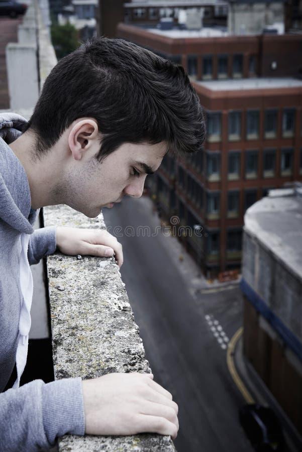 Jeune homme déprimé contemplant le suicide sur Buildin grand images stock