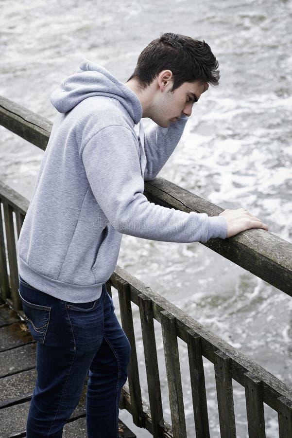 Jeune homme déprimé contemplant le suicide sur le pont au-dessus de la rivière image stock
