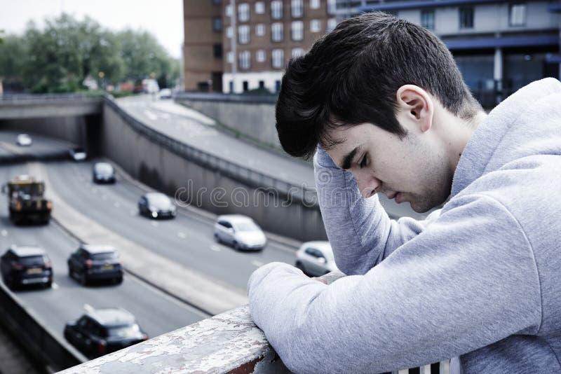 Jeune homme déprimé contemplant le suicide sur le pont en route images stock
