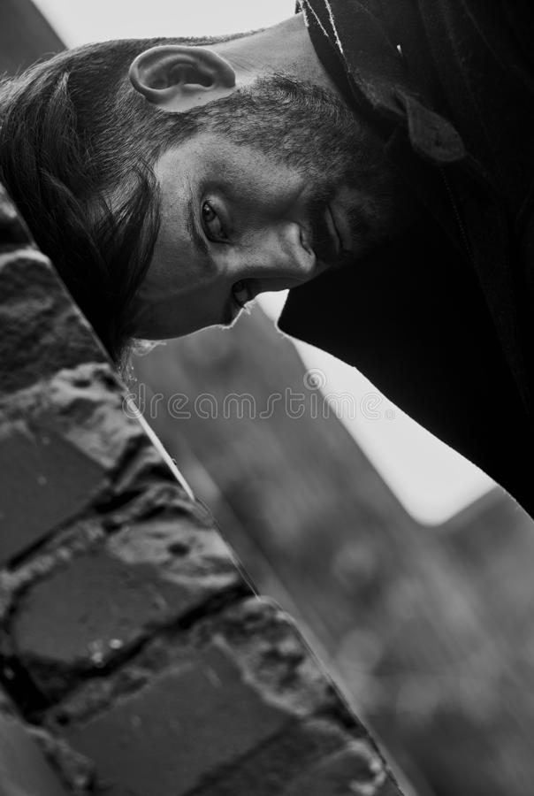 Jeune homme déprimé frustrant près du mur de briques semblant fâché closeup image libre de droits