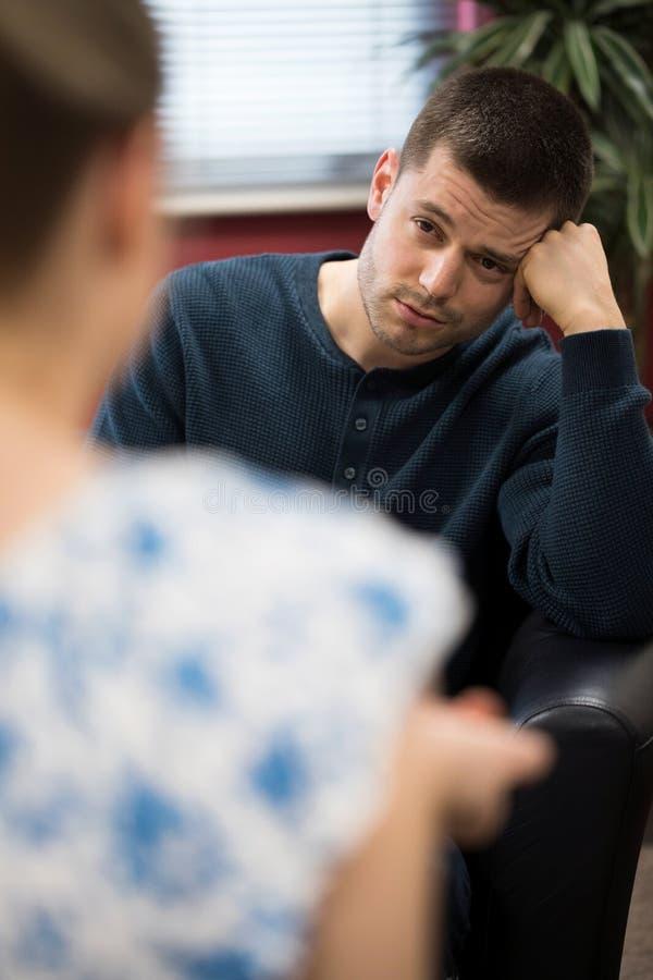 Jeune homme déprimé parlant au conseiller image stock