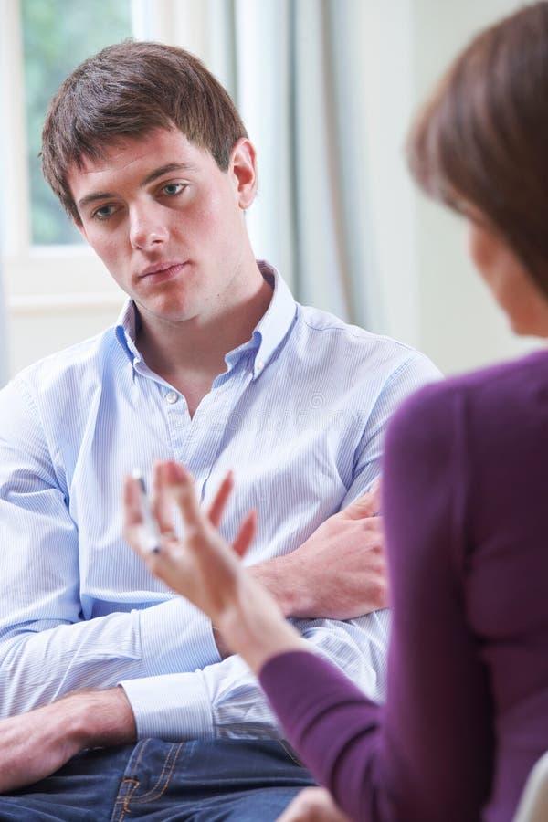 Jeune homme déprimé parlant au conseiller photo stock