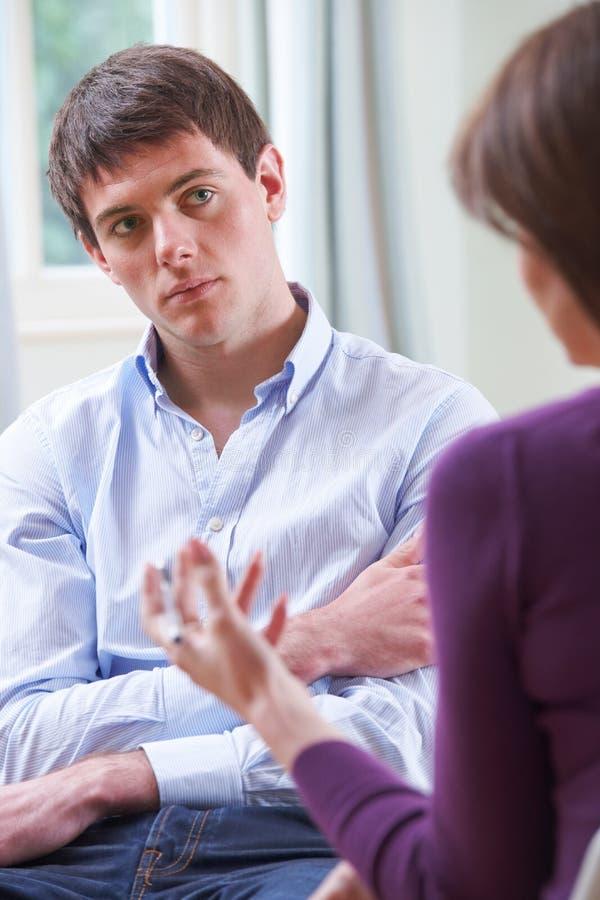 Jeune homme déprimé parlant au conseiller photos stock