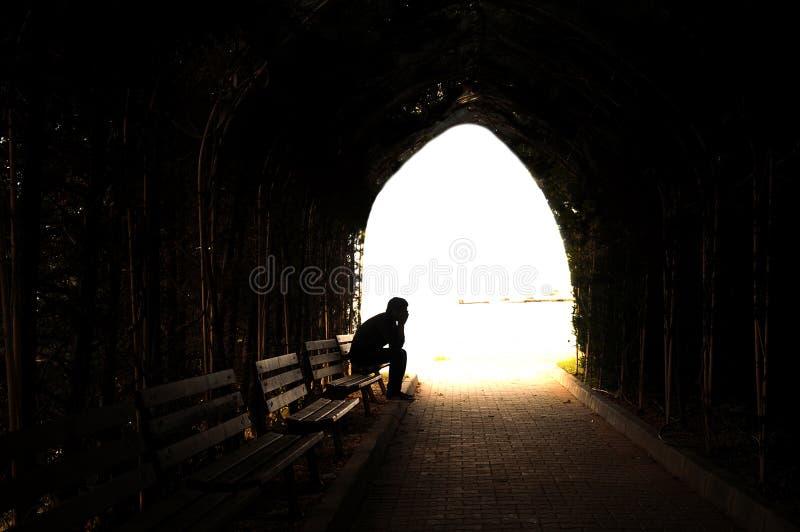Jeune homme déprimé s'asseyant sur le banc photographie stock