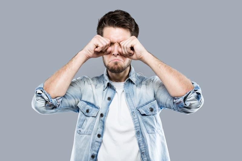 Jeune homme déprimé souffrant de la couverture d'inquiétude son visage au-dessus de fond gris images stock