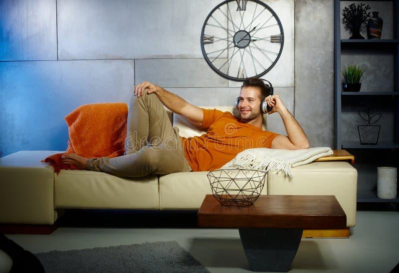 Jeune homme détendant à la maison image stock