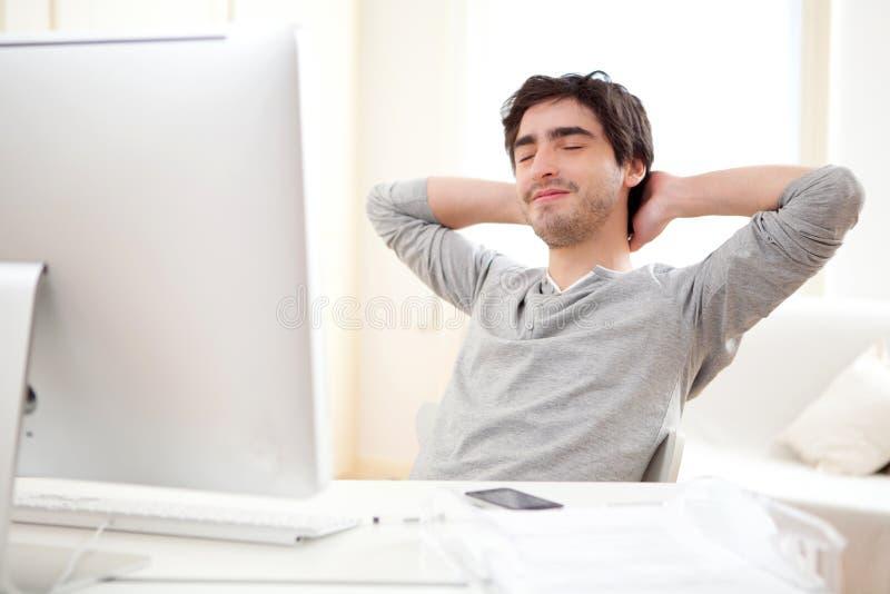 Jeune homme détendant pendant une coupure au bureau photo stock