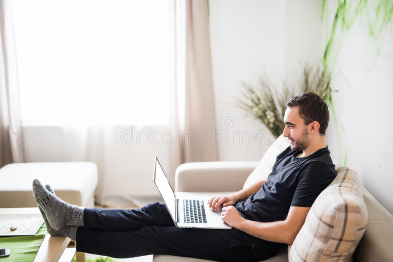 Jeune homme détendant sur le sofa avec un ordinateur portable à la maison images stock