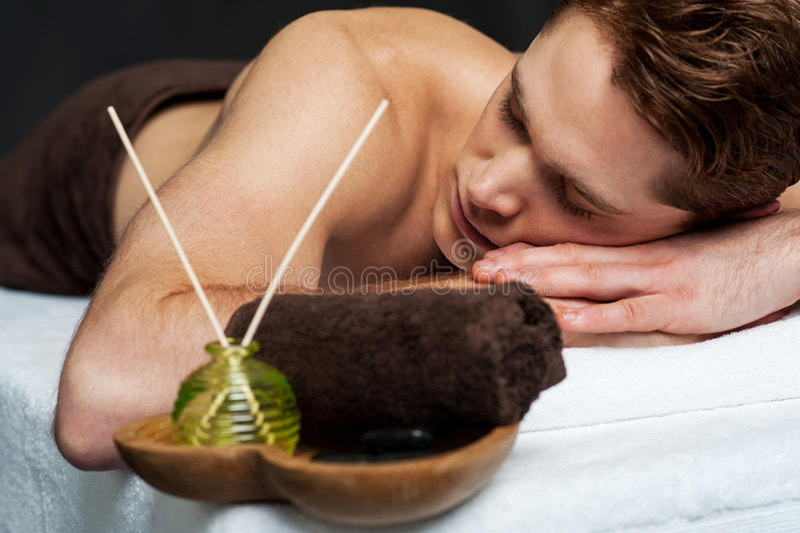 Jeune homme détendant sur le Tableau de massage photo stock
