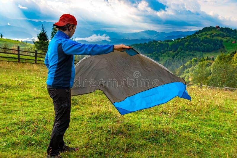 Jeune homme dévoilant en bas d'une couverture en nylon imperméable pour se reposer sur l'herbe, dans un beau paysage de montagne  images stock