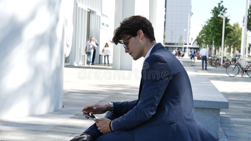 Jeune homme d'affaires à l'aide de la tablette extérieure photographie stock libre de droits