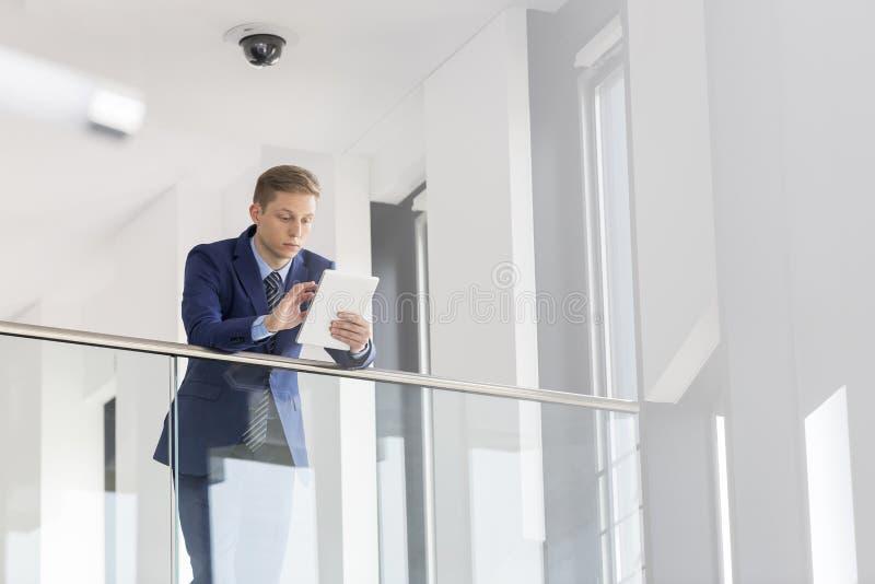 Jeune homme d'affaires à l'aide du comprimé numérique tout en se penchant sur la balustrade au bureau images stock