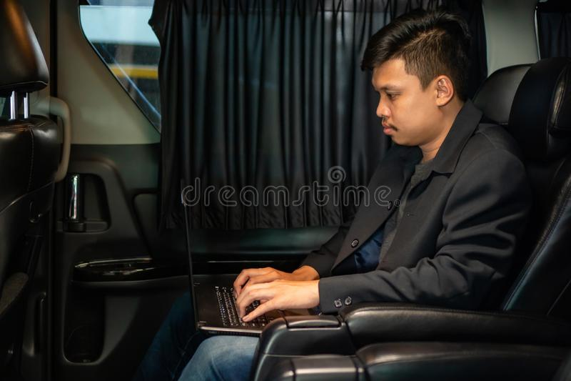 Jeune homme d'affaires à l'aide du téléphone portable et de l'ordinateur portable dans la voiture photos libres de droits