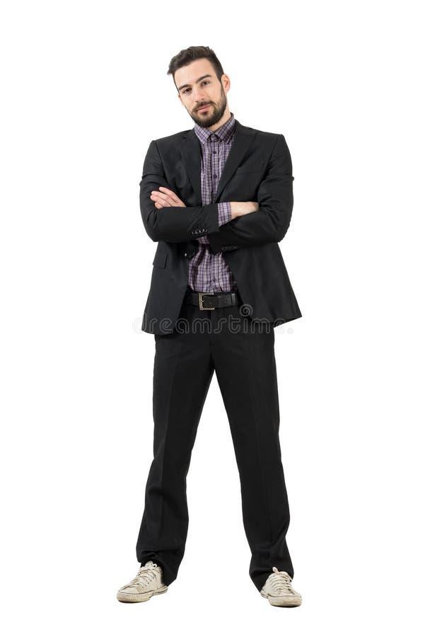 Jeune homme d'affaires à la mode barbu dans le costume et espadrilles avec les bras croisés photos libres de droits