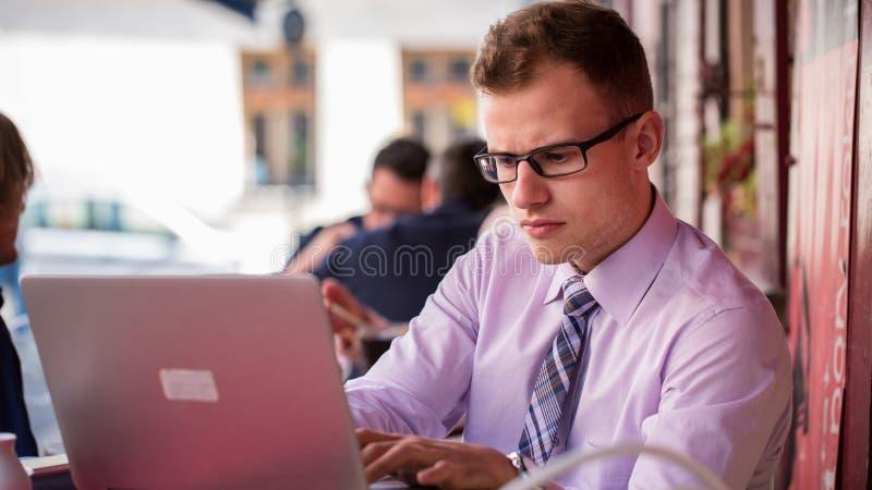 Jeune homme d'affaires à la mode dans une chemise et un portrait de lien. Il est travail photos stock