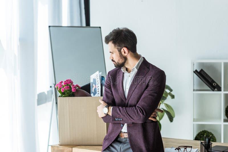 jeune homme d'affaires écarté regardant la boîte de substance personnelle images libres de droits