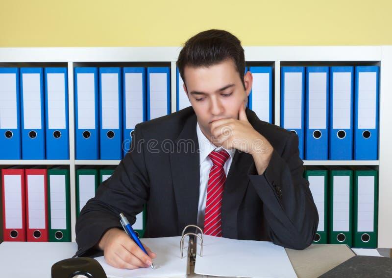 Jeune homme d'affaires écrivant une note au bureau image stock
