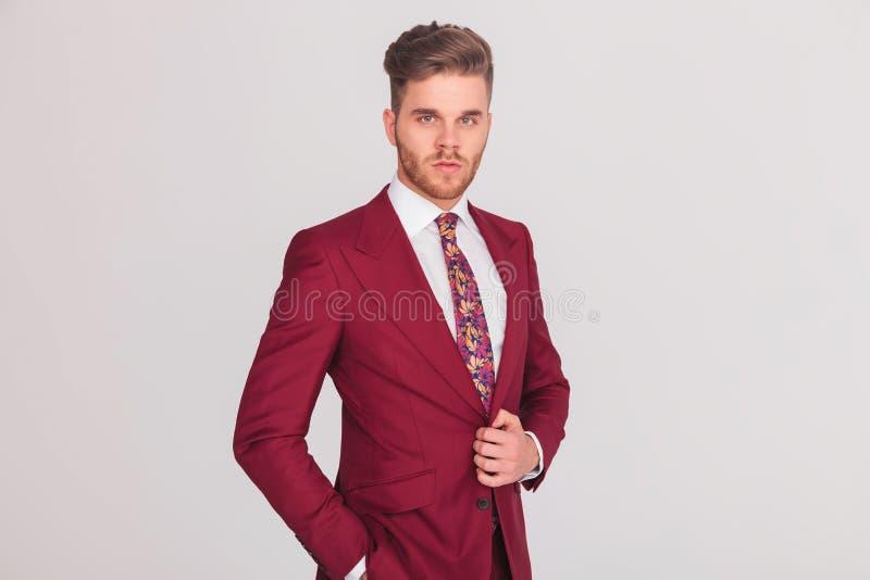 Jeune homme d'affaires élégant sûr se tenant sur le fond gris images stock