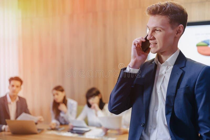 Jeune homme d'affaires élégant utilisant une veste et une chemise sur le fond d'un bureau fonctionnant avec des personnes parla photographie stock libre de droits