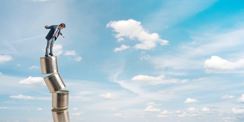Jeune homme d'affaires équilibrant sur une pile de boîtes en fer blanc photo libre de droits