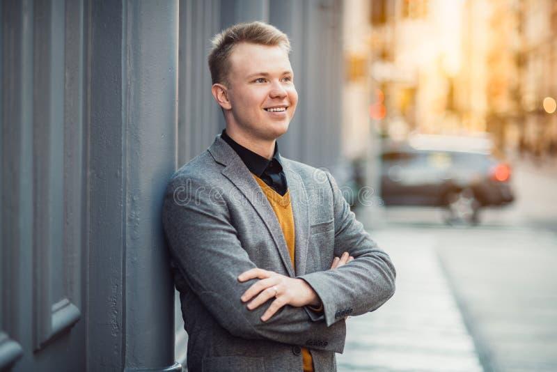 Jeune homme d'affaires adulte de sourire bel se tenant dehors près du mur sur la rue de ville photographie stock libre de droits