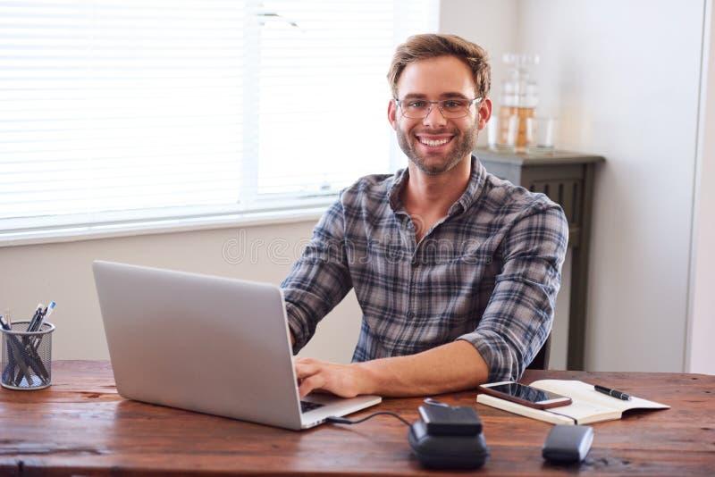 Jeune homme d'affaires adulte souriant à l'appareil-photo tout en se reposant au bureau image stock