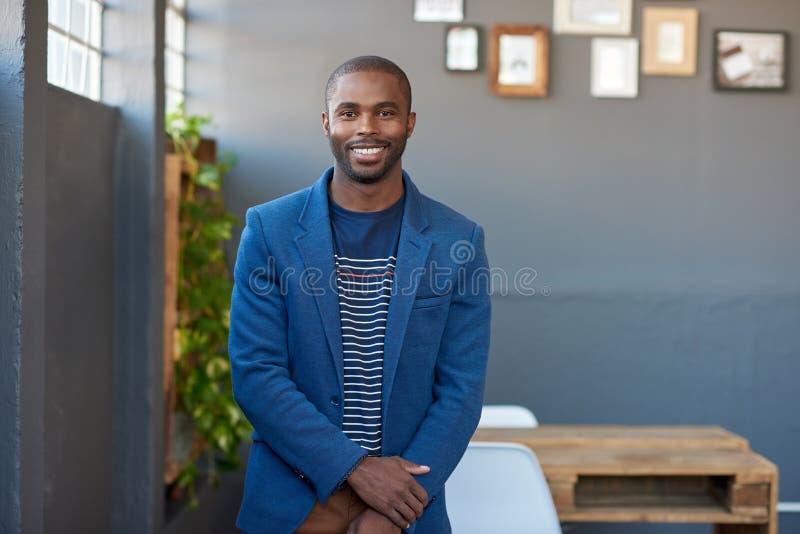 Jeune homme d'affaires africain de sourire seul se tenant dans un bureau photographie stock