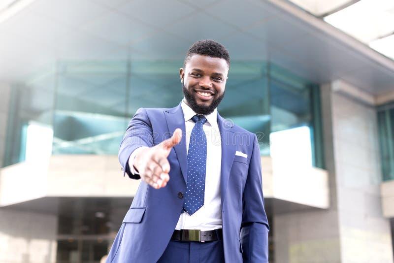 Jeune homme d'affaires africain prolongeant sa main pour saluer de nouveaux associés financiers photographie stock