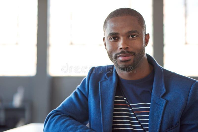 Jeune homme d'affaires africain sûr seul se tenant dans un bureau image libre de droits