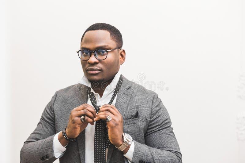 Jeune homme d'affaires d'Afro-américain dans un costume gris attachant un lien sur un fond blanc images stock