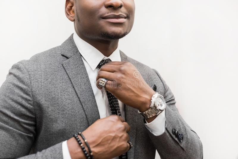 Jeune homme d'affaires d'Afro-américain dans un costume gris attachant un lien sur un fond blanc photos stock
